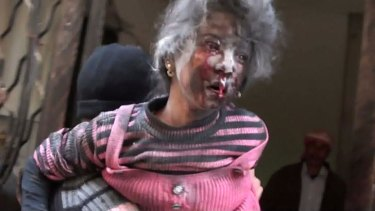 Casualty: An image grab taken from a video uploaded on YouTube shows a man carrying an injured girl in the rebel-held city of Rastan, central Syria.