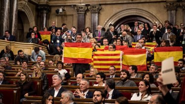 Partido Popular de Catalunya (Popular Party of Catalonia) members of Catalan parliament brandish Spanish flags at the end of the parliamentary session on Monday in Barcelona.