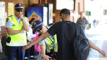 Police search a man at Footscray railway station.