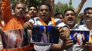 Indian activists of the right-wing Hindu organisation Shiv Sena hold photocopies of models wearing swimwear featuring Hindu goddess Lakshmi during a demonstration in Amritsar on Sunday.