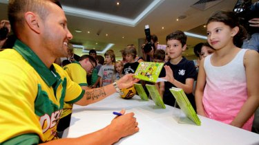 """Retired Broncos player Scott Prince and Logan deputy principal David Hartley sign books for young fans Ned, 7, and sister Milly, 9, Naouri, from Annerley, at the launch of """"Deadly D and Justice Jones - Making the Team"""""""