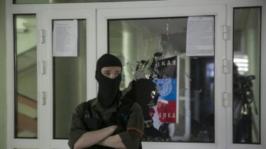 A pro-Russian masked man stands watch inside the Mariupol town hall in east Ukraine.