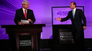 Opposition Leader Tony Abbott notices Prime Minister Kevin Rudd arrived with notes at the first leaders' debate.