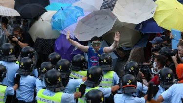 Defiant stand: A pro-democracy demonstrator gestures in front of police near the Hong Kong government headquarters.