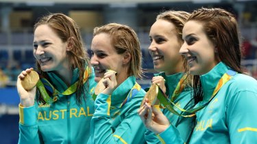 Australia's Cate Campbell, Bronte Campbell, Emma McKeon and Brittany Elmslie, from left, hold their gold medals after winning the women's 4x100-meter freestyle final setting a new world record.