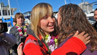 Abby Sunderland, left, 16, gets a hug from friend Casey Nash, right, before leaving for her world record attempting solo journey around the world.