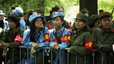 Volunteers in Chinese Red Army-style uniforms wait to meet Chen Guangbiao.