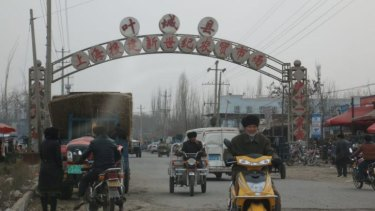 A sign above a road in Xinjiang's Kargilik county publicises investment in the area from Shanghai.