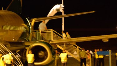 The first group of asylum seekers board a plane at Christmas Island bound for Papua New Guinea under the government's hardline solution to deal with boat arrivals.