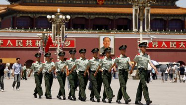 Policemen march in front of the giant portrait of Chairman Mao Zedong in Tiananmen Square.