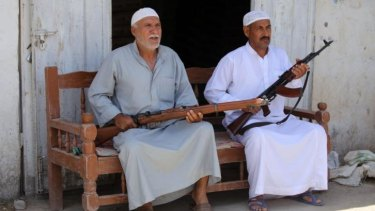 Iraqi men sit with their weapons in the Iraqi town of Jdaideh in  Diyala province on June 14 after they volunteered to join the fight following the call to arms by Shiite cleric Grand Ayatollah Ali al-Sistani.