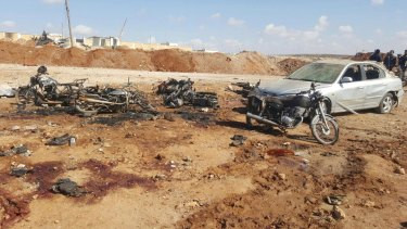 This image released by the Thiqa News Agency shows damaged motorcycles and a car following a suicide blast in Sousian village, about eight kilometres north of al-Bab, Syria on Friday.