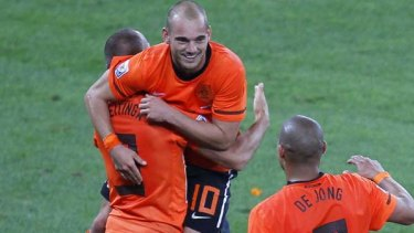 Centre of attention ... Wesley Sneijder celebrates with teammates John Heitinga and Nigel de Jong after scoring against Slovakia.