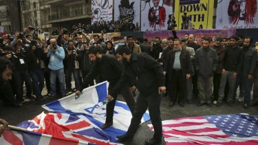 Iranian demonstrators pour petrol on the US, British and Israeli flags at a rally  in Tehran last month.
