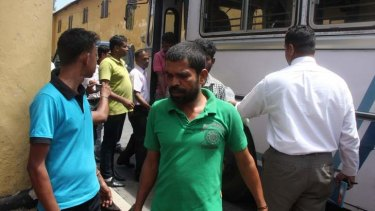 An asylum seeker is delivered to court at Galle by Sri Lankan navy personnel.