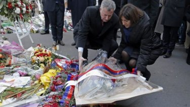 New York City Mayor Bill de Blasio, left, and Paris mayor Anne Hidalgo, right, lay a wreath of flowers at the site of the <i>Charlie Hebdo</i> newspaper attack, in Paris.