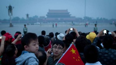 Generational ties ... a child waves a flag at the national flag raising ceremon in Tiananmen Square.