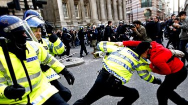 A demonstrator scuffles with police during protests outside the Bank of England into London.