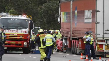 Loss … police and rescue staff investigate a crash on the Hume Highway, south of Sydney, after a semi-trailer collided with a red Ford, killing all three occupants.