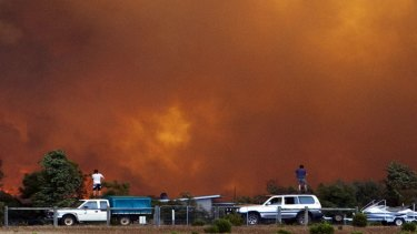 Residents watch a bushfire from the top of their cars in Margaret River.