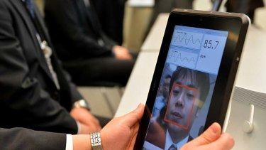 A Fujitsu engineer demonstrates how a smartphone that can take the pulse of a user works.
