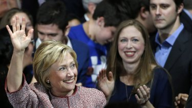 Democratic presidential candidate Hillary Clinton waves to supporters as she enters the room with daughter Chelsea.