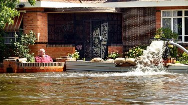 A Numurkah resident tries to protect his home with sandbags and a pump as water rises around him.