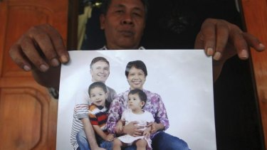 Widi Yuwono, the brother of Yuli Hastini, right, shows her sister's family portrait with her Dutch husband John Paulissen and their two children Arjuna and Sri