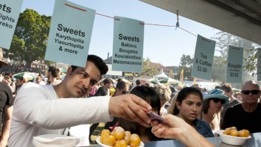 A man pays for honey puffs at Paniyiri, Australia's longest running Greek Festival, held at Musgrave Park in Brisbane on May 19, 2012.