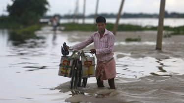 Floods displace thousands: A man pushes his bicycle past a flooded road in Ashigarh village, about 70 kilometers east of Gauhati, India.