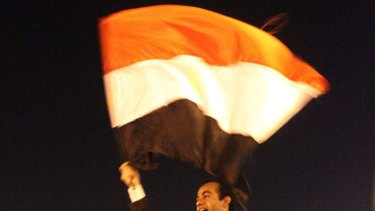 Flying the flag for change ... Abdullah al-Qadi waves the Egyptian flag while being carried by anti-government demonstrators during celebrations of his wedding to Sonia al-Beali in Tahrir Square in Cairo.