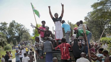 Demonstrators climb aboard a military truck as they celebrate what they perceive to be an attempted military coup d'etat, with army soldiers riding in an armoured vehicle in the capital Bujumbura, Burundi.