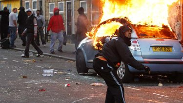 A rioter throws a rock at riot police in Clarence Road in Hackney.