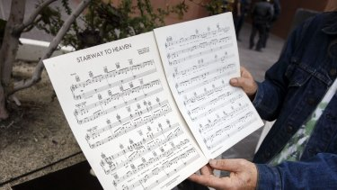 A Led Zeppelin fan holds up sheet music for <i>Stairway to Heaven</i> outside of federal court in Los Angeles.