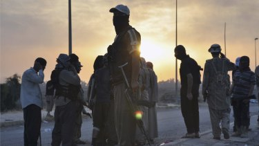 Islamic State fighters stand guard at a checkpoint in the northern Iraq city of Mosul.