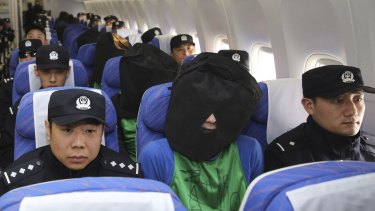 Chinese suspects involved in wire fraud, centre, sit in a plane as they arrive at Beijing Airport on Wednesday.