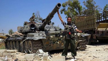 A rebel fighter with a tank reportedly confiscated from an army barracks. The US has sharply toughened its line on Syria, promising the rebels weapons for the first time.