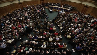 Members vote on handsets to decide whether to give final approval to legislation introducing the first women bishops, during a meeting of the General Synod of the Church of England in London.
