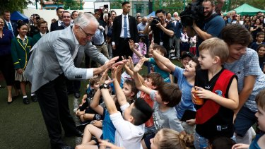 The Prime Minister gives high-fives to children at the school.