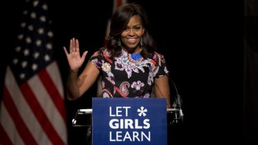 US first lady Michelle Obama waves as she receives a rock star reception by school girls at Mulberry School for Girls before taking part in a question and answer session in east London.