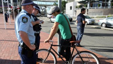On patrol ... officers speak to an unhelmeted cyclist near Pyrmont Bridge, Sydney.