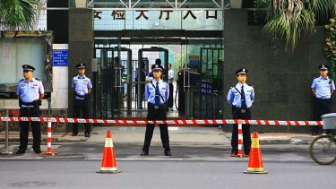 Police officers stand outside court for the trial of Chongqing's police chief Wang Lijun.