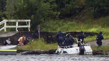 A swat team aim their weapons while people take cover during a shoot out at Utoeya island.