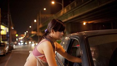 Not all is as it seems: Shao Lin, 25, and a mother of three, serves a customer on a highway in Taoyuan.