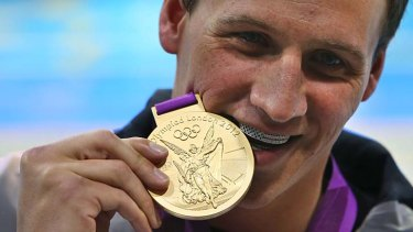 Golden boy: Ryan Lochte wears a US$25,000 American flag grill as he bites into his gold medal at the 2012 London Olympics.