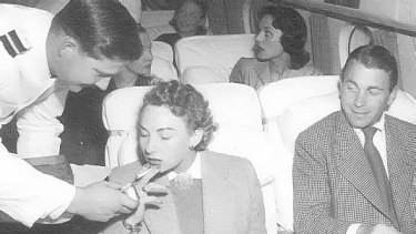 How it once was: A Qantas steward helps a passenger light up.