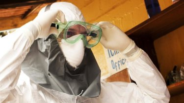 A health worker in a protective suit prepares for a shift at an Ebola isolation ward at a mission hospital outside of Monrovia, Liberia.