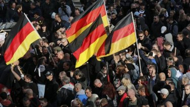 "Nationalist gathering: People carrying German flags join a demonstration by ""hooligans against Salafists and Islamic State extremists"" in Cologne."