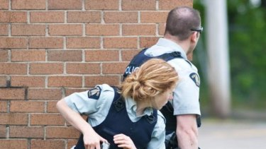 Police keep watch on a house in Moncton, New Brunswick during a search for a heavily armed gunman suspected of killing three Canadian policemen.