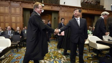 Japanese's Chief Negotiator Koji Tsuruoka, right, shakes hand with General Counsel of Australia Bill Campbell, left, before the International Court of Justice delivers its verdict in The Hague, Netherlands.